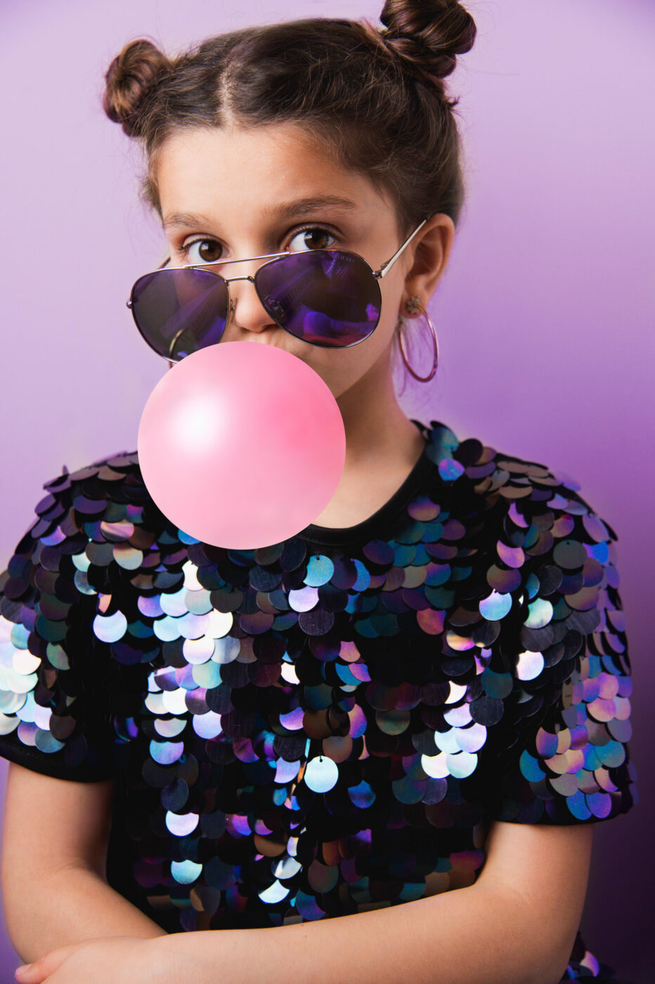 Girl in sequins and sunglasses blowing a bubble - Vanessa Guzzo Photography