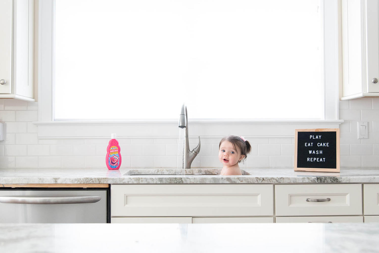 Baby taking a bath in the kitchen sink - Vanessa Guzzo Photography